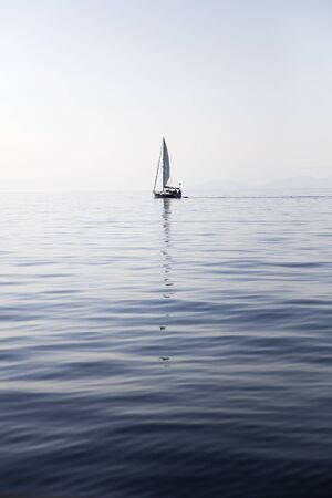 Sailing boat on a calm sea surface with reflection in the water