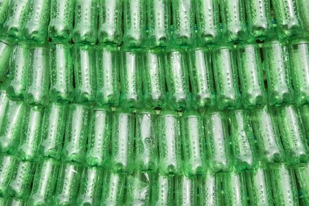 Backdrop of green plastic bottles stacked next to each other
