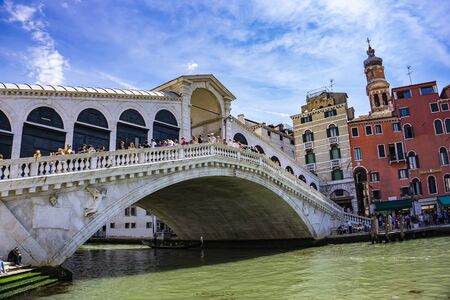 VENICE, ITALY - MAY 26, 2019: Unidenified people by Rialto Bridge in Venice, Italy. Rialto Bridge is the oldest of the four bridges spanning the Grand Canal in Venice, Italy.