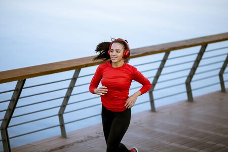 View at active young beautiful woman running on the promenade along the riverside