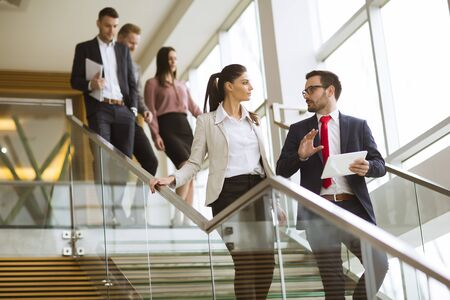 Young business partners analyze the business results while walking down the stairs in modern office
