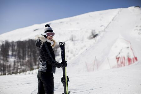 Happy young woman with ski equipment spending winter vacation at mountain resort