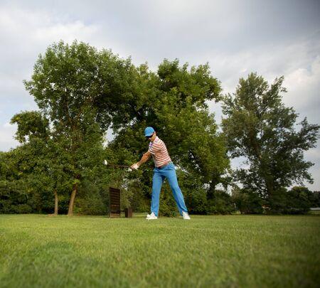 Jonge man spelen op de golfbaan Stockfoto