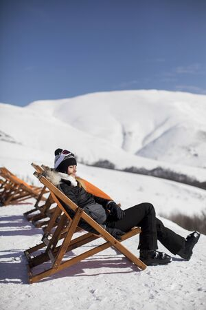 Young woman skier relaxing in a lounge chair after skiing in the mountains in winter Banco de Imagens