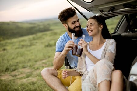 坐在汽车手套的爱恋的年轻夫妇在旅行期间在自然期间