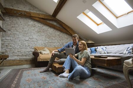 Happy young couple using tablet sitting on the floor at home Stock Photo