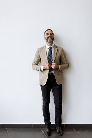 Portret of bearded handsome middle-aged  businessman by the wall 版權商用圖片