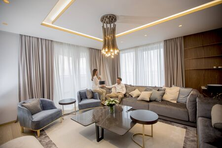Young couple sitting and relaxes in the luxury living room