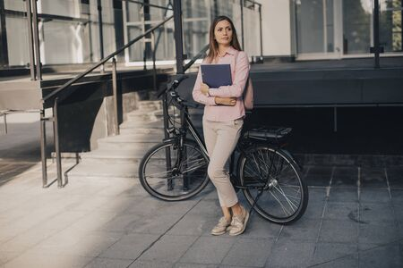 Young woman with files in the  hands standing outdoor in front of electric bike 写真素材