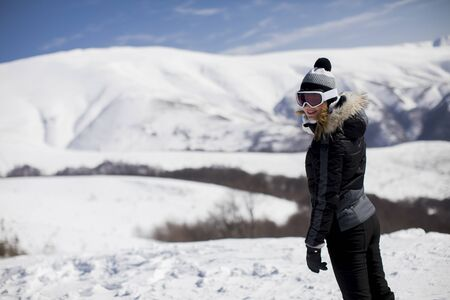 Young woman stands on a snowy  mountain slope in her ski suit in the day