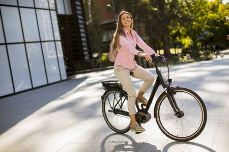 Young woman riding an electric bicycle in urban environment