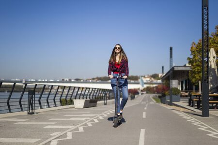 Pretty young woman riding an electric scooter in the street on a sunny day