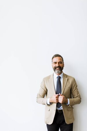 Portret of bearded handsome middle-aged  businessman by the wall Stock Photo