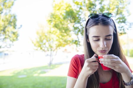 Portrait of young woman drinking coffee in the park Imagens
