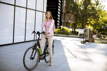 Young woman with ebicycle using on mobile phone outdoor