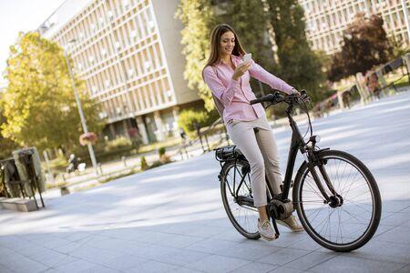 Hübsche junge Frau, die ein Elektrofahrrad fährt und Handy in der städtischen Umgebung benutzt Standard-Bild