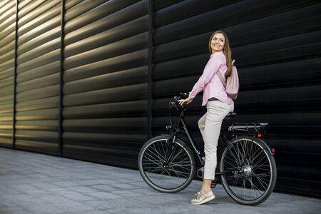 Hübsche junge Frau mit modernem Elektro-E-Bike für die Stadt als sauberer, nachhaltiger Stadtverkehr