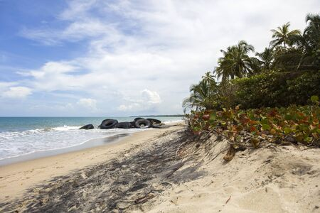 Tires on the tropical sandy beach as pollution concept