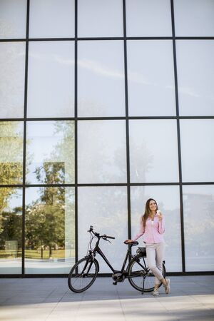 Beautiful young female cyclist drinks coffee from a cup by the electric bicycle in the urban environment Imagens