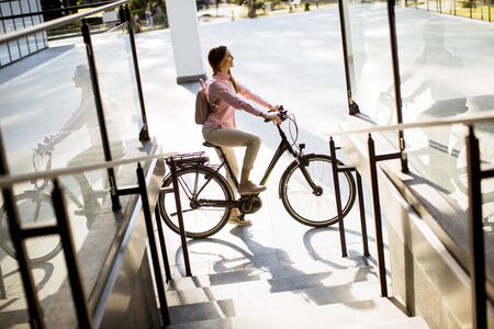Pretty young woman with modern city electric e-bike clean sustainable urban transportation