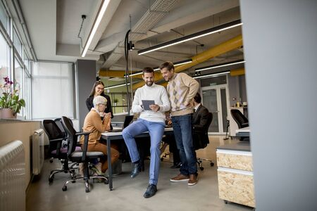 Two businessmen with a digital tablet in front of their team at the modern office