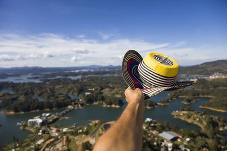 View at hand with Colombian hat over the Guatape lake in Antioquia, Colombia