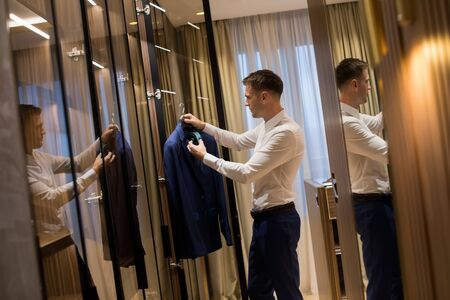 Handsome young man choosing clothes from  wardrobe in the hall of contemporary apartment