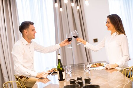 Sweet young couple having a romantic dinner and toasting with glasses of red wine at luxury kitchen