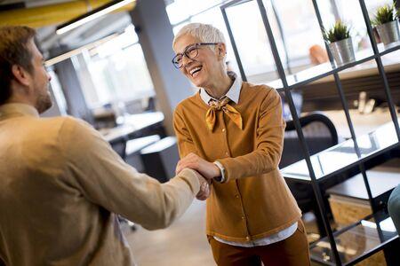Grateful senior  businesswoman  boss lady hold hand of best employee,  shake hands warm welcoming standing in coworking space Banco de Imagens