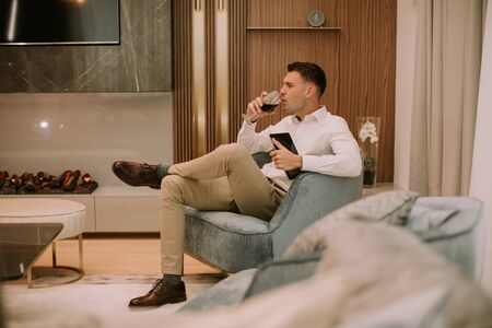 Young man sits in a luxury apartment, drinking red wine and holding a digital tablet