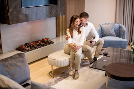 Young couple having a romantic evening with a glass of red wine at home in the luxury contemporary living room