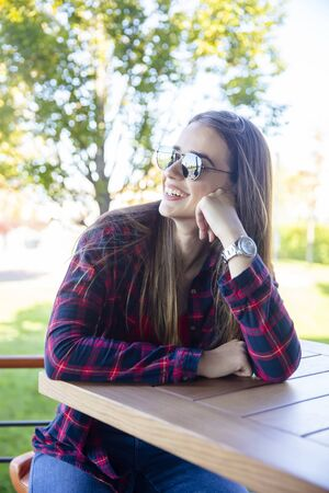 Portrait of a young woman wearing sunglasses sitting in the park on a bench Banco de Imagens