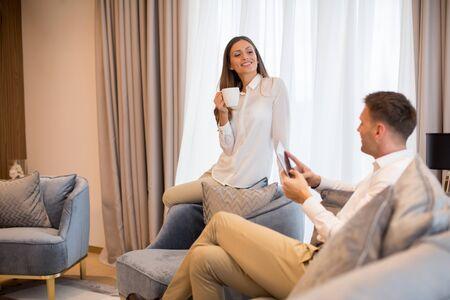 Pareja joven tomando café y usando tableta digital en el lujoso apartamento contemporáneo
