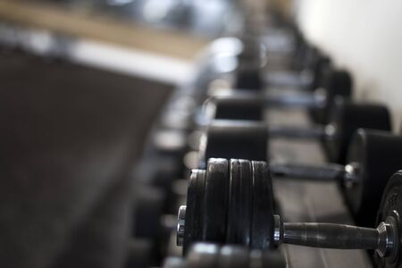 Closeup at the row of metal dumbbells on rack in the gym