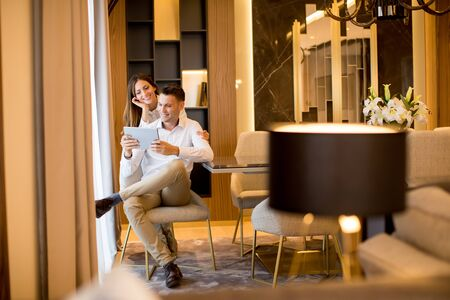 Young couple relaxing at home and using digital tablet in the living room by the window