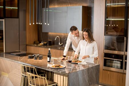 Sweet young couple having a romantic dinner at luxury kitchen Banco de Imagens