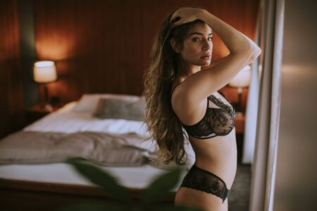 Beautiful young woman in lingerie looking outside the window in her beautiful apartment Banco de Imagens