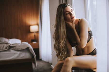 Beautiful young woman in lingerie sitting and looking outside the window in her beautiful apartment Banco de Imagens