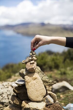 Femlae hand doing stone stacking at Isla del Sol on Titicaca lake Standard-Bild