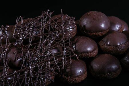 Small round chocolate cakes on the dark background Фото со стока