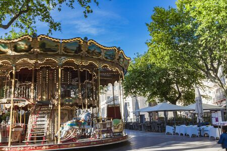 AVIGNON, FRANCE - APRIL 28, 2019: Carrousel Belle Epoque merry-go-round in the historical city centre in Avignon, France. This beautiful traditional carousel is located at Place de l'Horloge in Avignon. Editorial