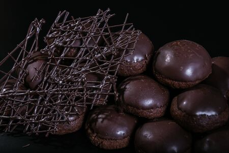 Small round chocolate cakes on the dark background 写真素材