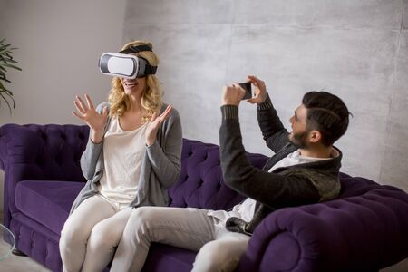Young couple sitting in the room while young woman wearing a virtual reality glasses