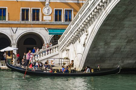 VENICE, ITALY - OCTOBER 12, 2019: Unidentified people by Rialto Bridge in Venice, Italy. It is the oldest of the four bridges spanning the Grand Canal in Venice. Editoriali