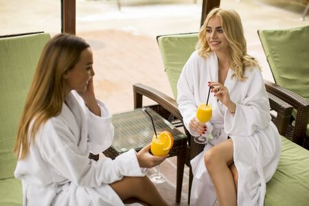 Cheerful young women in bathrobes drinking juice in spa center