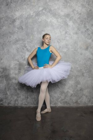 Pretty young ballerina dancer dancing classical ballet against rustic wall