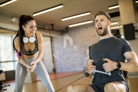 Handsome young man using seated row machine in the gym with support of female coach