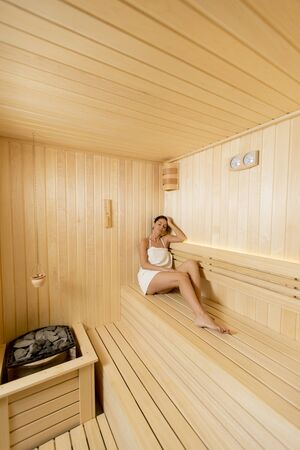 Pretty young woman relaxing in the sauna 免版税图像