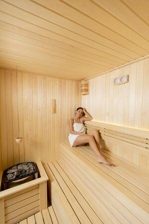 Pretty young woman relaxing in the sauna Standard-Bild