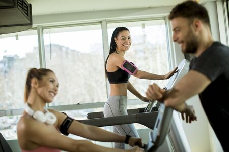 Personal trainer with pretty young woman on cycling machine at the gym 免版税图像